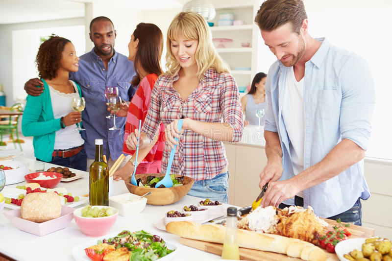 group-friends-having-dinner-party-home-getting-food-ready-kitchen-35610836